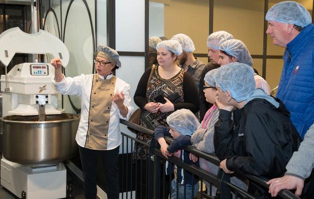 Groep mensen krijgt uitleg bij een bakmachine tijdens de Siroopwafel Experience in Gouda